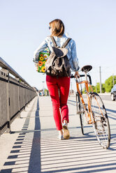 Young woman with bicycle on pavement holding gift box - UUF004736
