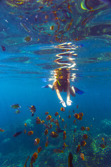 Indonesia, Bali, young woman snorkeling with fish - KNTF000059