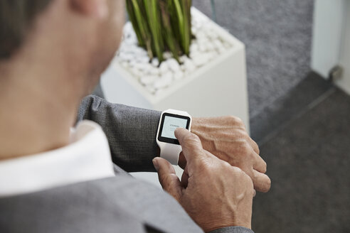 Businessman in office looking at smartwatch - PDF000986