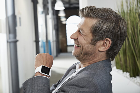 Smiling businessman in office with smartwatch - PDF000981