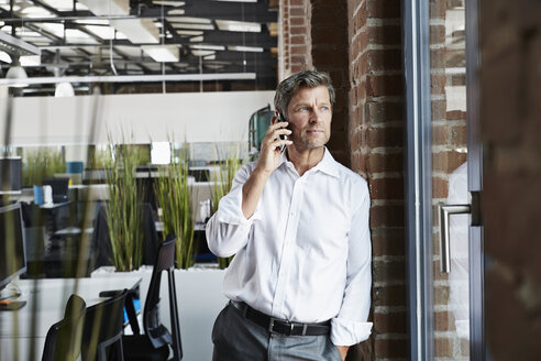 Businessman in office on smartphone looking out of window - PDF000997