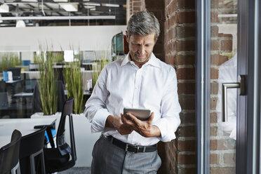 Businessman in office looking at digital tablet - PDF000994