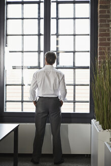 Businessman in office looking out of window - PDF000999
