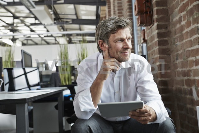 Businessman in office with digital tablet looking to the side - PDF001041