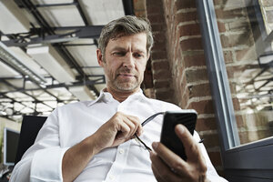 Businessman in office looking at smartphone - PDF001010