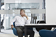 Smiling businessman sitting on conference room - PDF001012