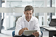 Businessman in office looking at digital tablet - PDF001018