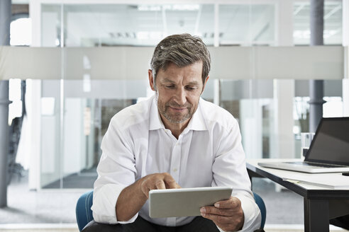 Businessman in office looking at digital tablet - PDF001018