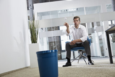 Businessman in office throwing crumpled paper in wastepaper basket - PDF001021