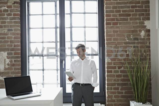 Businessman at the window looking at digital tablet - PDF001024