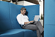 Smiling businessman sitting in conversation pit in office using laptop - PDF001027