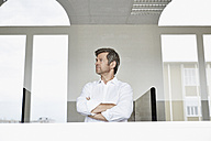 Businessman behind glass pane in office - PDF001036