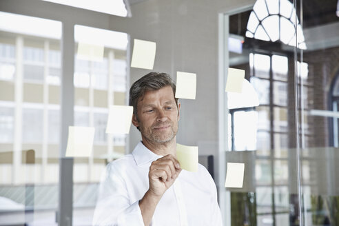 Businessman with sticky notes on glass pane in office - PDF001045
