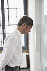 Frustated businessman in office leaning head against a wall - PDF001048