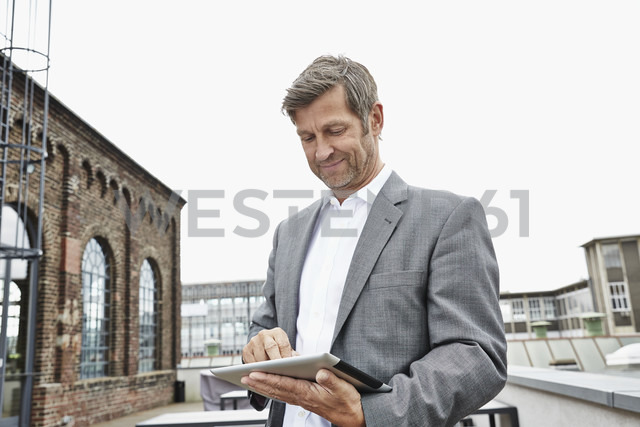 Smiling businessman using digital tablet on roof terrace - PDF001051