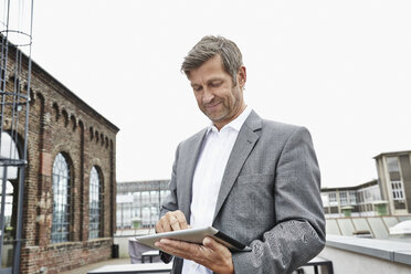 Smiling businessman using digital tablet on roof terrace - PDF001051