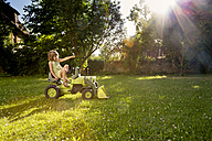 Little girl playing with toy tractor in a garden - LVF003501