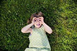 Little girl lying on a meadow looking through her fingers - LVF003504