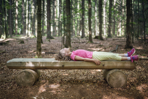 Girl lying on wooden bench in forest looking up - MW000086