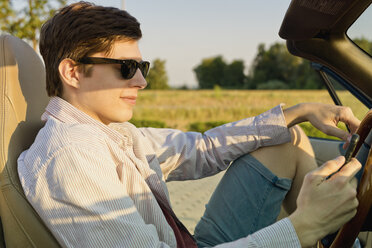 Teenager with sunglasses looking at his smartphone in a convertible car - MSF004632