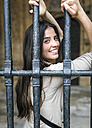 Spain, Oviedo, portrait of smiling young woman behind grid - MGOF000288