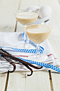 Two glasses of egg liqueur, ribbon and vanilla beans on cloth - SBDF002026