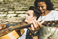 Relaxed young couple with guitar outdoors - UUF004752