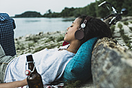 Relaxed young woman with headphones by the riverside - UUF004755