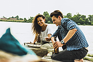 Happy young couple having a barbecue by the riverside - UUF004761
