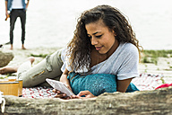 Relaxed young woman with digital tablet outdoors - UUF004774