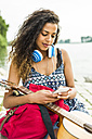 Young woman with headphones, guitar, cellphone and backpack by the riverside - UUF004791