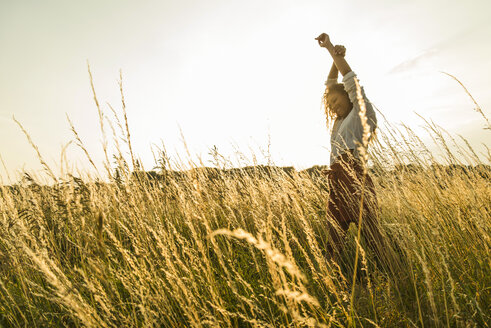Young woman standing with raised arms in field with tall grass - UUF004830