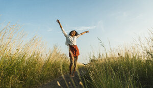 Young woman standing with outstretched arms on path in field - UUF004832