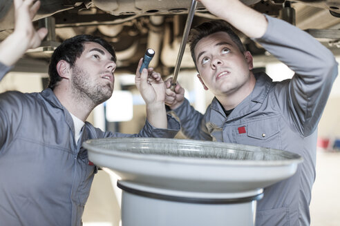 Two car mechanics at work in repair garage - ZEF005678