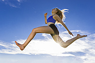 Young athlete jumping under blue sky - STSF000812