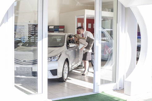 Car dealer showing new car to woman in showroom - ZEF006650