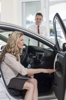 Woman examining new car in showroom - ZEF006354