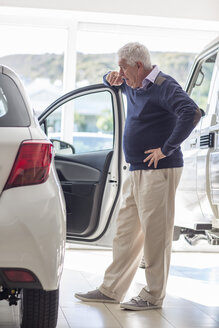 Senior man looking at a new car in showroom - ZEF006374