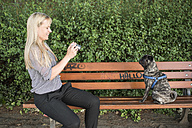 Smiling woman sitting on a bench taking a photo of her pug - PAF001446