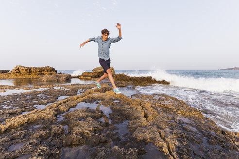Greece, Rhodes, young man jumping on rocks at seafront - WDF003143