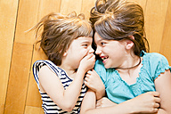 Two sisters lying face to face on wooden floor - LVF003515