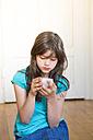Girl sitting on wooden floor using smartphone - LVF003528