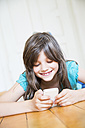 Smiling girl lying on wooden floor using smartphone - LVF003535