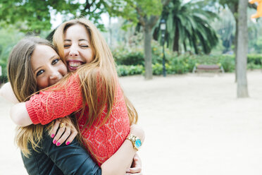 Two happy young women hugging in a park - GEMF000244