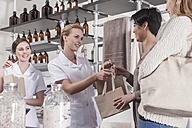 Shop assistant in wellness shop handing over bag to client - ZEF006517