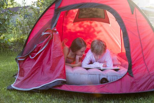 Boy and girl reading lying in a red tent with a book - SARF001930