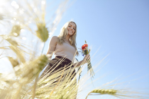 Smiling young woman with bunch of field flowers standing in a rye field - BFRF001238