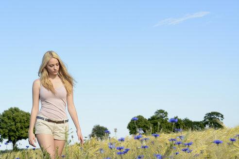 Germany, woman walking along a field - BFRF001252