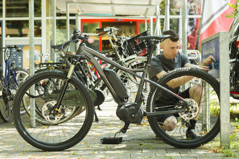 Electric mountainbike, young man on charging station - SG001727