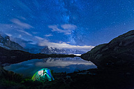 France, Mont Blanc, Lake Cheserys, lit tent on the shore of the lake by night with Milky way and Mount Blanc reflected in the lake - LOMF000004